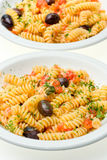 Fusilli with cheese, fresh tomatoes and olives. Stock Image