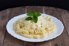 Fusilli with Creamy Sauce, Cheese and Mint Leaves. Fusilli Pasta with Creamy Sauce, Yellow Cheese and Fresh Mint Leaves on a Vintage Wooden Table Royalty Free Stock Images