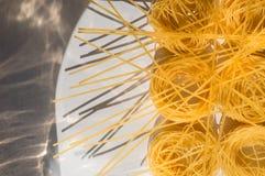 Fusilli ed i nidi della pasta hanno sparso a caso sulla tavola bianca Fotografia Stock