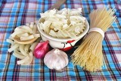 Fusilli, espaguetis, ajo de los macarrones, y chalotes en tela Imágenes de archivo libres de regalías