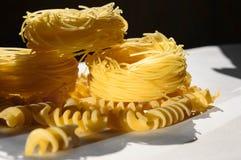 Fusilli et pâtes nichent sur la table blanche avec le fond noir Photo stock