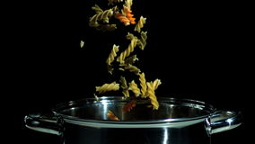 Fusilli falling in pot on black background. In slow motion stock video footage