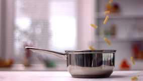 Fusilli falling in pot in kitchen. In slow motion stock video