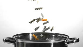 Fusilli falling into a saucepan in black and white. In slow motion stock footage