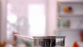 Fusilli falling into saucepan in kitchen. In slow motion stock video