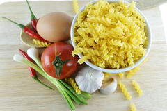 Fusilli, garlic, chili, onion, egg and tomato on  wooden. Fusilli, garlic, chili, onion, egg and tomato on wooden on white background Royalty Free Stock Photography