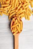 Fusilli italian pasta lying in wooden spoon Stock Image