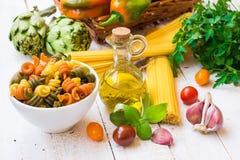 Fusilli italiano dos espaguetes da massa, garrafa do azeite, manjericão, tomates de cereja, alho, ervas e vegetais, ingredientes  Fotografia de Stock