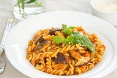 Fusilli with mushroom in tomato sauce. Fusilli with mushroom and tomato sauce in a dish with basil on top Stock Photo