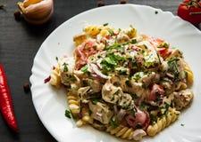 Fusilli-Nudelsalat mit Tomate, der Hühnerbrust, Zwiebel und Olive mit Soße in der Platte Lizenzfreies Stockfoto
