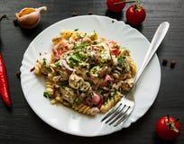 Fusilli-Nudelsalat mit Tomate, der Hühnerbrust, Zwiebel und Olive mit Soße in der Platte Stockbilder