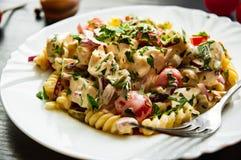 Fusilli-Nudelsalat mit Tomate, der Hühnerbrust, Zwiebel und Olive mit Soße in der Platte Lizenzfreie Stockfotos