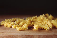 Fusilli pasta. Dried fusilli pasta on a wooden chopping board Stock Photos