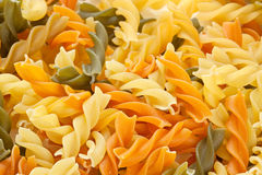 Fusilli pasta background. Multicolored pasta with the addition of natural tomatoes and spinach Stock Photo