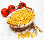 Fusilli pasta. Basket with fusilli pasta and tomato on a old wooden table Stock Photo