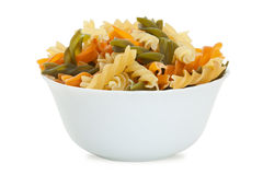 Fusilli pasta in bowl. Multicolored pasta with the addition of natural tomatoes and spinach Stock Photo