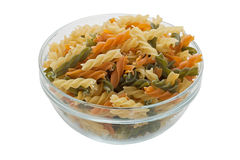 Fusilli pasta in bowl (with clipping path). Multicolored pasta with the addition of natural tomatoes and spinach Royalty Free Stock Images