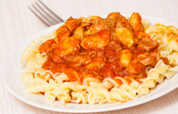 Fusilli pasta with chicken in tomato sauce Stock Images