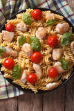 Fusilli pasta with chicken, tomatoes and basil close-up. vertica Stock Images