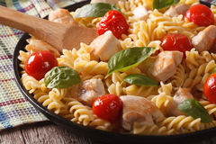 Fusilli pasta with chicken and tomatoes close-up. horizontal Royalty Free Stock Images