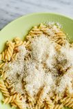 Fusilli Pasta. Close up of delicious home made fusilli pasta with parmesan cheese and olive oil decorated with fresh basil on black slate Cacio e Pepe royalty free stock photo