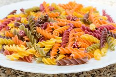 Fusilli pasta colored background. Classic Italian pasta in the f. Orm of a spiral of durum wheat. Raw pasta is put on a plate. Pasta from flour with additives of Royalty Free Stock Photography