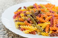 Fusilli pasta colored background. Classic Italian pasta in the f. Orm of a spiral of durum wheat. Raw pasta is put on a plate. Pasta from flour with additives of Stock Image
