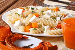 Fusilli pasta with feta and pumpkin close-up and juice Stock Images