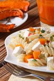 Fusilli pasta with feta and pumpkin on a plate close up. Vertica Stock Image
