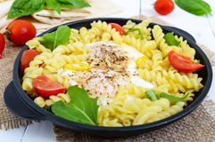 Fusilli pasta, fried eggs and tomatoes. Royalty Free Stock Photos