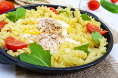 Fusilli pasta, fried eggs and tomatoes Royalty Free Stock Photo