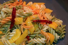 Fusilli pasta with garlic, dried red chili, yellow pepper and olive oil being cooked in a pan Stock Photo