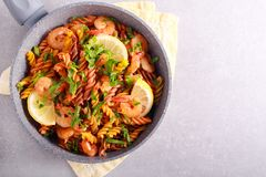 Fusilli pasta with lemony shrimps. In a frying pan stock photo