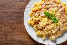 Fusilli pasta med Carbonara sås och ost i den vita plattan på trätabellen arkivfoto