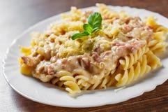 Fusilli pasta med Carbonara sås och ost i den vita plattan på trätabellen royaltyfri foto