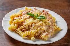 Fusilli pasta med Carbonara sås och ost i den vita plattan på trätabellen royaltyfri fotografi