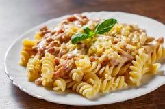 Fusilli pasta med Carbonara sås och ost i den vita plattan på trätabellen arkivbild