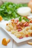 Fusilli pasta med champinjoner och bacon Arkivfoto