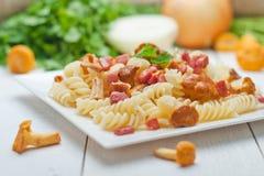 Fusilli pasta med champinjoner och bacon Fotografering för Bildbyråer