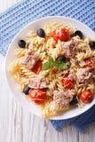 Fusilli pasta med tonfisk, tomater och parmesancloseupen vertikalt Arkivfoton