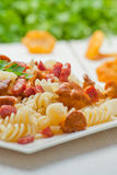 Fusilli pasta with mushrooms and bacon. Stock Photo