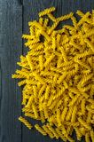 Fusilli pasta on a old wooden background. Italian cuisine. Vertical view stock photo
