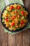 Fusilli pasta with pork, broccoli, tomatoes and cheese cheddar c. Lose-up on the table. Vertical view from above stock images