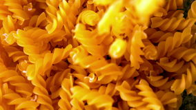 Fusilli pasta pouring onto more stock video footage
