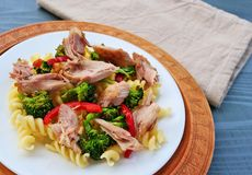 Fusilli pasta with pulled chicken meat, broccoli and vegetables on white plate stock photo
