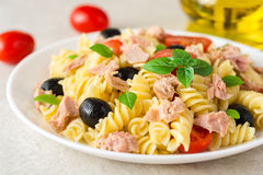 Fusilli pasta salad with tuna, tomatoes, black olives and basil on gray stone background Royalty Free Stock Photography