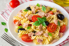 Fusilli pasta salad with tuna, tomatoes, black olives and basil on gray stone background. Selective focus stock photography