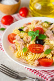 Fusilli pasta salad with tuna, tomatoes, black olives and basil on gray stone background. Selective focus royalty free stock photos