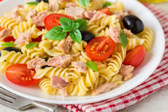 Fusilli pasta salad with tuna, tomatoes, black olives and basil on gray stone background. Selective focus stock photos