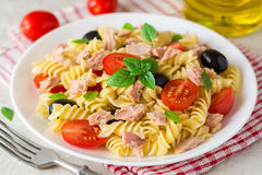 Fusilli pasta salad with tuna, tomatoes, black olives and basil on gray stone background. Selective focus stock photo